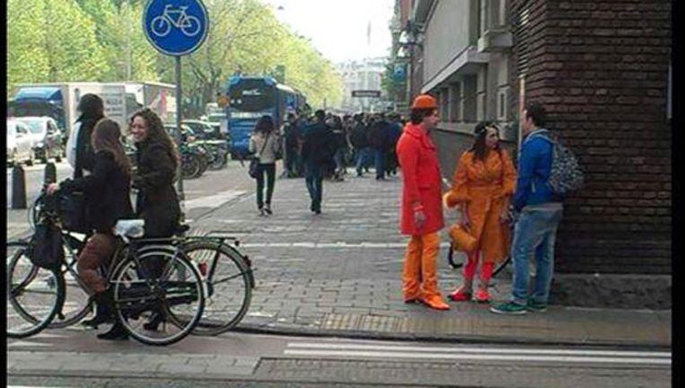 Foto van oranje geklede toeristen vandaag in Amsterdam. Beeld Twitter / 3 op Reis