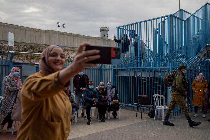 Sur cette photo d'archive du 23 février 2021, une Palestinienne prend un selfie après avoir reçu le vaccin contre le coronavirus d'une équipe médicale israélienne au poste de contrôle de Qalandia entre la ville de Ramallah en Cisjordanie et Jérusalem.