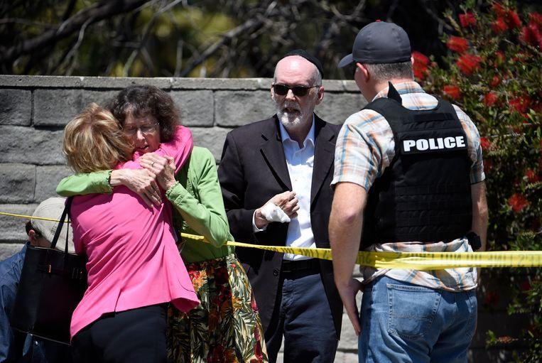 Mensen zoeken troost bij elkaar in de buurt van de synagoge. De politie heeft de omgeving afgezet.