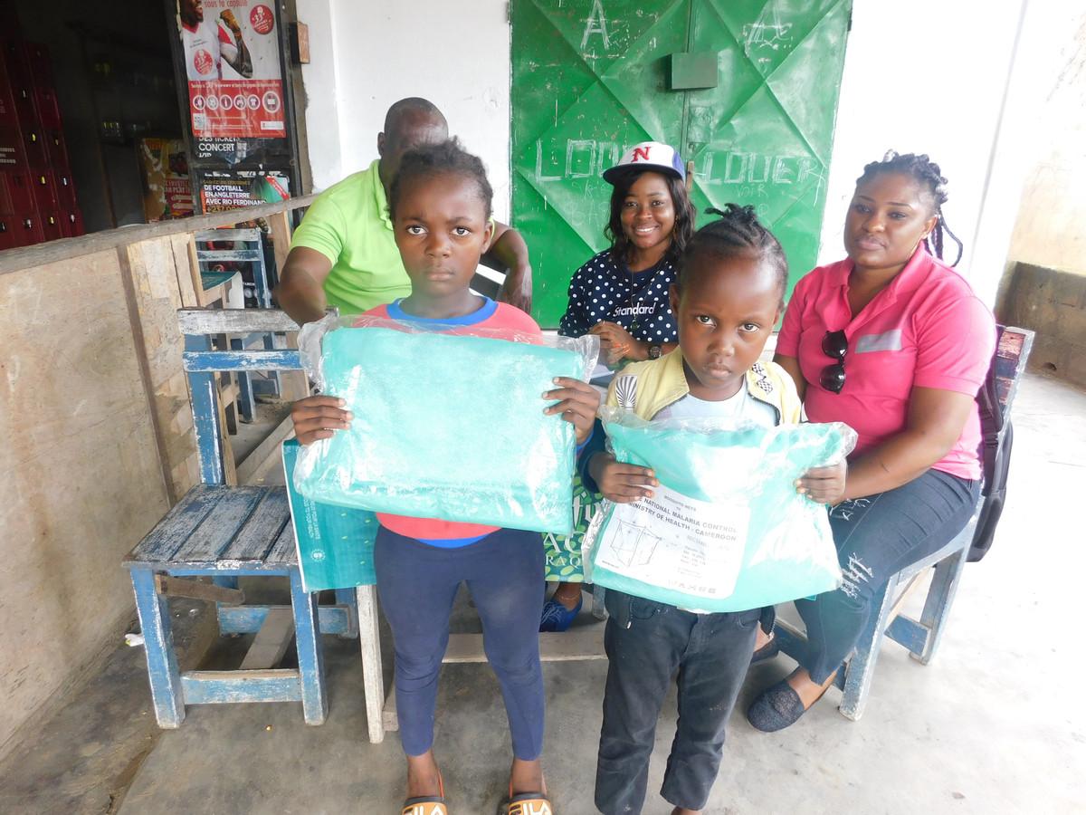 Kinderen uit de omgeving van Bomono tonen muskietennetten die ze van de Casey Troy Foundation gekregen hebben.