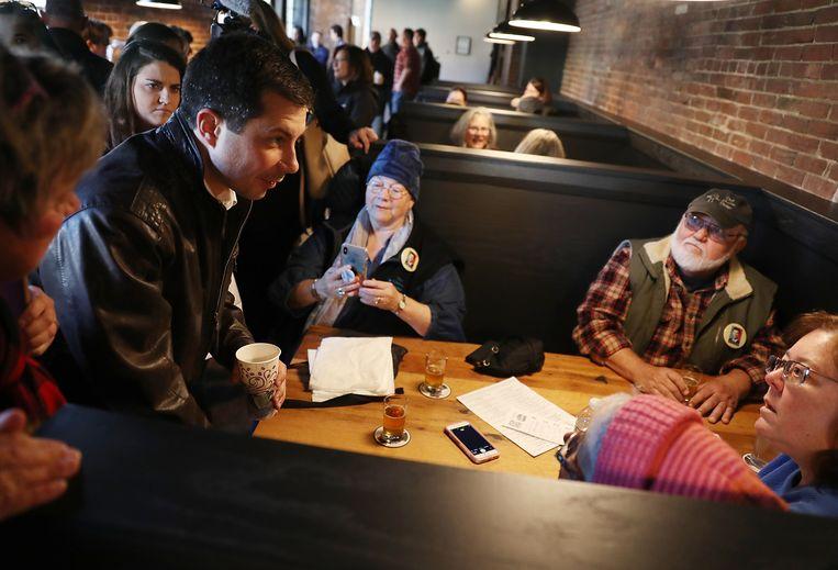 Buttigieg praat met klanten van een restaurant in New Hampshire, de staat die als tweede stemt in de Democratische voorverkiezingen. In een CNN-peiling in Iowa in het weekeinde ging hij aan kop met 25 procent, gevolgd door senator Elizabeth Warren met 16 procent en oud-vicepresident Joe Biden met 15 procent. Beeld AFP