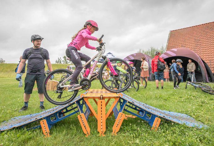 Niek Vermeulen (links) van de stichting Fietsen op Tholen kijkt hoe Fleur Otte (8) uit Tholen de hindernis op fietst.
