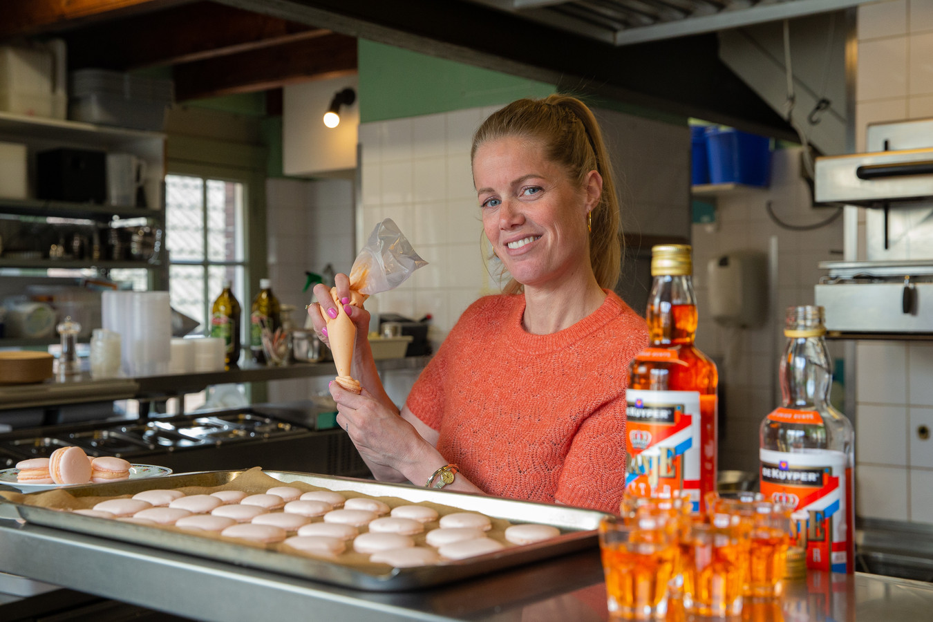 Mede-eigenaar Eva Wolvenne van Café Verheyden bezig met het maken van oranje macarons in de aanloop naar Koningsdag.