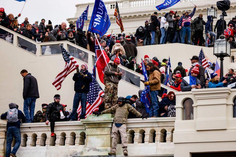 Het Amerikaanse parlementsgebouw wordt beklommen. Mensen zwaaien met Trump-vlaggen en met de omstreden Confederatievlag. Beeld Getty Images
