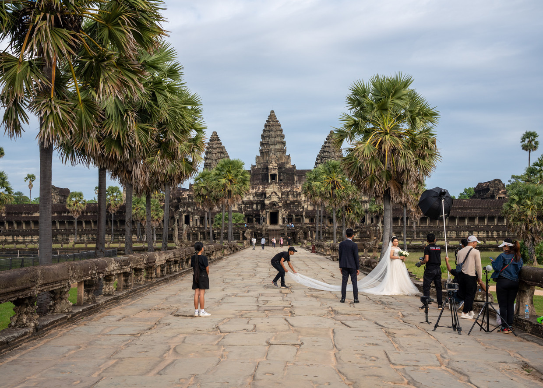 Voor een trouwreportage met de tempels van Angkor als decor neemt dit Cambodjaanse stelletje alle tijd. Vanwege de strenge coronamaatregelen zijn er amper toeristen.  Beeld Antoine Raab