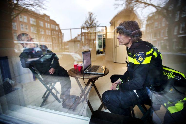 Wijkagent Wilco Berenschot praat met een buurtbewoner in zijn pop-up politiebureau in Rotterdam West, waar buurtbewoners binnenstappen voor een koffie, een praatje, een klacht of een probleem.  Beeld ANP
