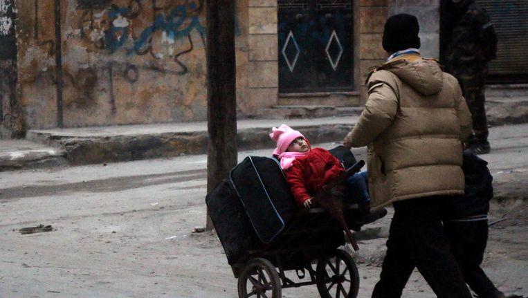 Syrische burgers ontvluchten de oostelijke wijken van Aleppo, de stad waar ook het gezin woont dat een visum voor ons land aanvroeg. Beeld AFP
