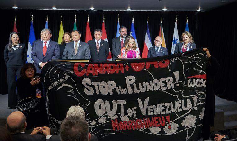 Demonstranten verstoren de persconferentie en houden een spandoek op met de tekst 'stop de plunderingen uit Venezuela'. Beeld EPA