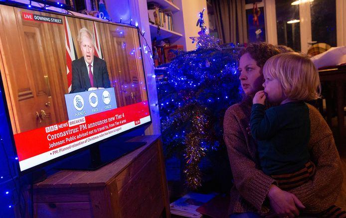 De Britse Leanne Hall en haar zoontje Alex kijken naar de speech van premier Boris Johnson over de nieuwe coronamaatregelen.