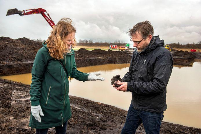 Jeroen van Leijsen van Staatsbosbeheer en Ellen van Aart van waterschap Brabantse Delta, bekijken een flinke kluit veen. Op de achtergrond de kraan die datzelfde veen uitgraaft.