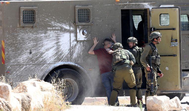 Israëlische militairen arresteren een Palestijn, in de stad Jenin. Beeld EPA