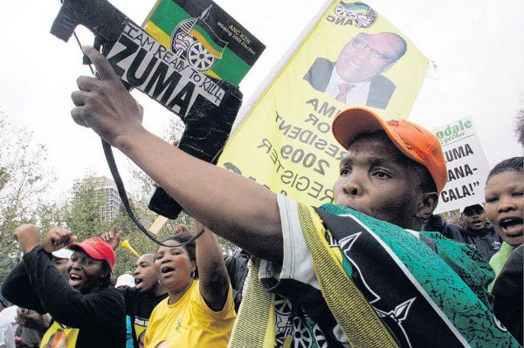 Aanhangers van Jacob Zuma in Pietermaritzburg. De jongen zwaait met een nepwapen met de tekst: 'Ik ben bereid om voor Zuma te doden'. Foto AP/Themba Hadebe Beeld