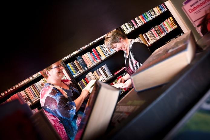 De vrijwilligers Diane Kuenen en Janetta Kleinmeulman van de Dorpsböke in Rekken tussen de boekenkasten van het minibibliotheekje in dorpshuis D'n Hof in Rekken.