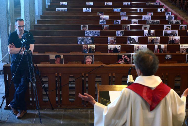 In Kerkdriel wonen gelovigen de dienst online bij, en hebben ze foto's ingestuurd voor in de kerk. Beeld Marcel van den Bergh / de Volkskrant