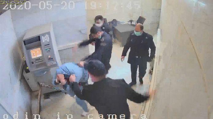 Enkele cipiers delen rake klappen uit aan een van de gevangenen.