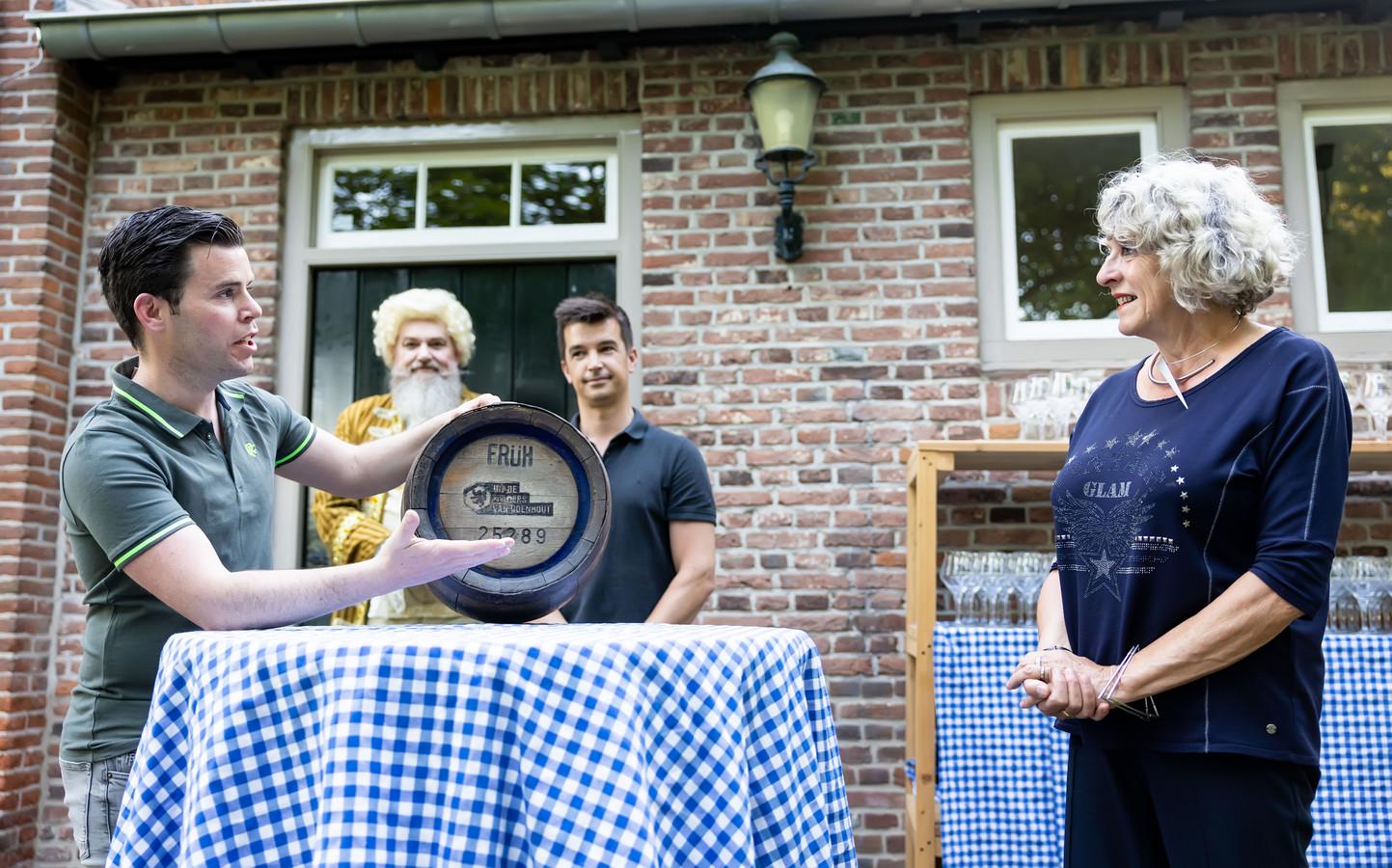 In Udenhout, bij kasteel Strijhoef werd het nieuw Udenhouts bier gepresenteerd. Stefan Ammerlaan (links) reikt het eerste vaatje uit aan Wilma de Jong, de nieuwe voorzitter van de dorpsraad. Koen Verbunt, naast De Jong, is de andere initiatiefnemer.