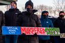 Demonstranten houden een bord omhoog op de wake voor Andre Hill op tweede kerstdag met de tekst 'Agent Adam Coy vermoordde Andre Hill'.