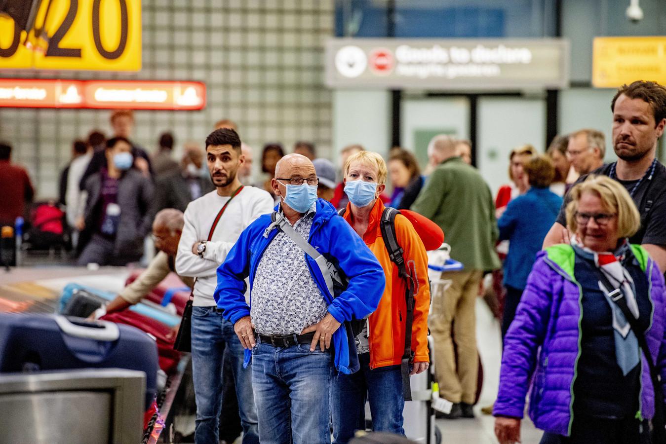 Reizigers wachten op hun bagage bij de bagageband. Meerdere luchtvaartmaatschappijen schrapten vluchten.