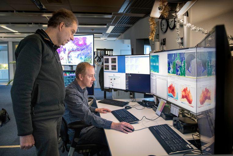 Geert Jan Oldenborgh (links) kijkt mee met meteoroloog Edwin Büscher naar de warmtekaart van Australië. Beeld Werry Crone