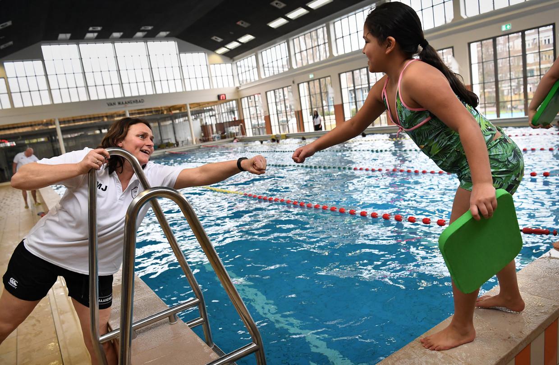 De badmeester geeft een leerling een boks voor ze het water induikt.  Beeld Marcel van den Bergh / de Volkskrant