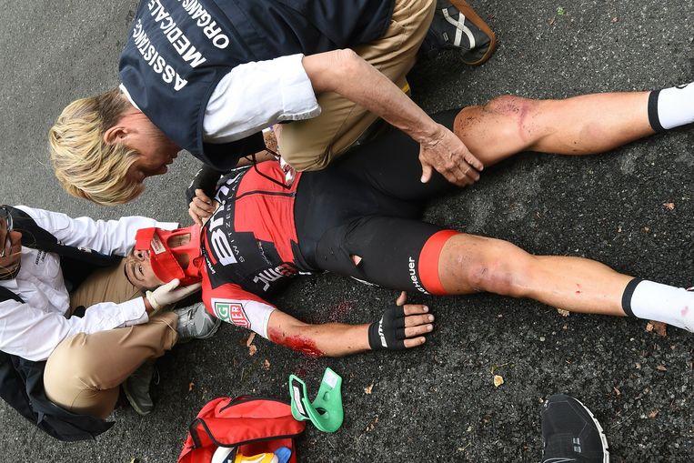 Richie Porte wordt geholpen door de Tour-artsen na zijn zware val in de negende etappe. Beeld Photo News
