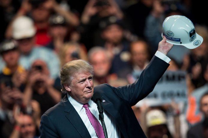 """Trump in mei 2016 op campagne met een mijnwerkershelm in Charleston, West Virginia. De toen nog presidentskandidaat beloofde de """"oorlog tegen steenkool"""" te beëindigen."""