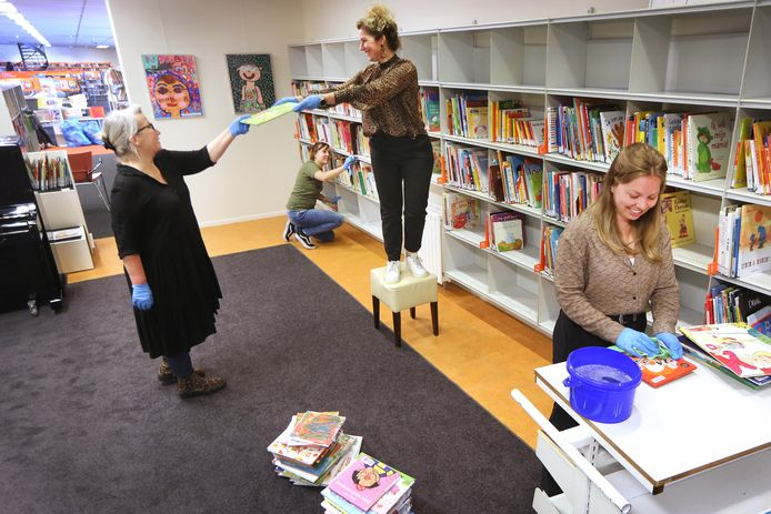 De medewerkers van de bibliotheek bereiden de heropening voor. Ook Willeke Rosdorff (op het krukje) steekt haar handen uit de mouwen.