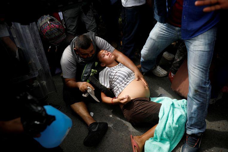 Een zwangere vrouw, die mee kwam met een migrantenkaravaan op weg naar de VS, heeft problemen in Metapa, Mexico (november 2018).  Aangezien baby's geboren in de VS automatisch staatsburger zijn, probeert het Witte Huis nu te beletten dat zwangere migranten het land binnenkomen. Beeld REUTERS