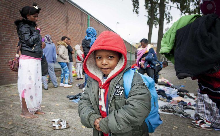 Vluchtelingen zoeken kleding uit die buurtbewoner hebben gebracht naast de Sportcentrum Schuttersveld, dat is ingericht als noodopvang. Beeld null