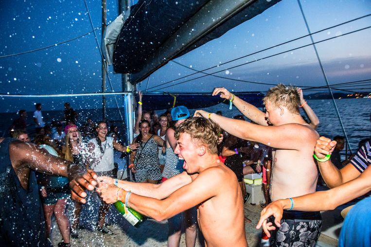 Feestende Nederlandse jongeren tijdens een Sunset Party Cruise voor de kust bij de Spaanse badplaats Blanes.  Beeld ANP