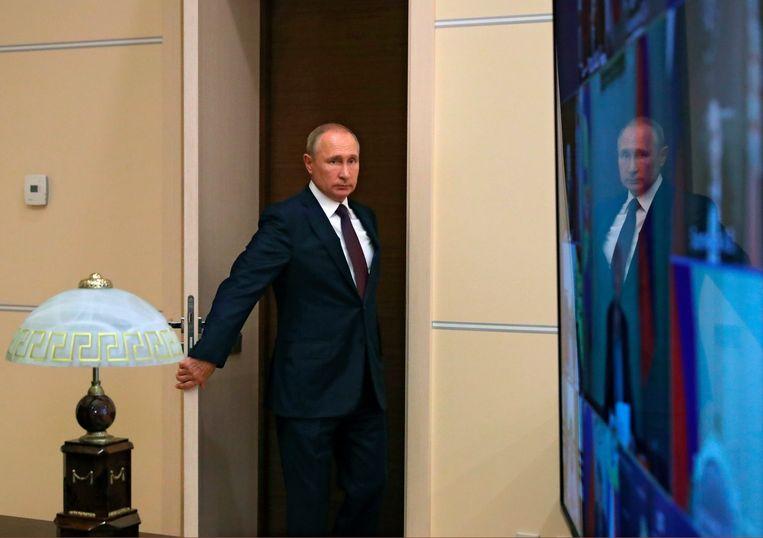 Vladimir Poetin stapt een vergaderzaal binnen voor een telebijeenkomst van de VN-Veiligheidsraad. Beeld AP