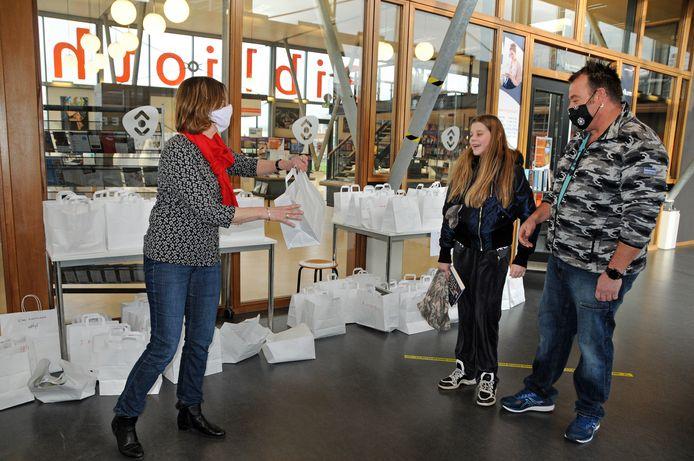 Bibliotheekmedewerker Marian Koene overhandigt een tasje leesvoer aan Marco en zijn dochter Amber Vrij uit Nieuwerkerk. Amber, die in groep 8 zit, haalt regelmatig boeken. Zeker nu in coronatijd