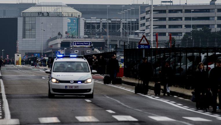 Reizigers lopen buiten bij luchthaven Brussel Beeld anp