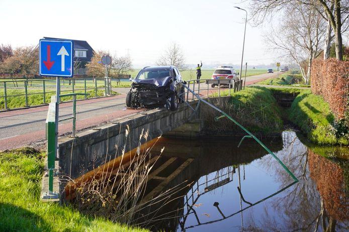 De brugleuning hangt in het water nadat een vrouw er met haar auto tegenaan is gereden.