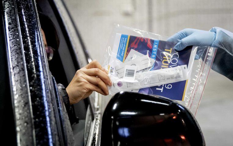Een bezoeker van een coronatestlocatie ontvangt een testkit om zelf thuis een coronatest te doen. Beeld ANP