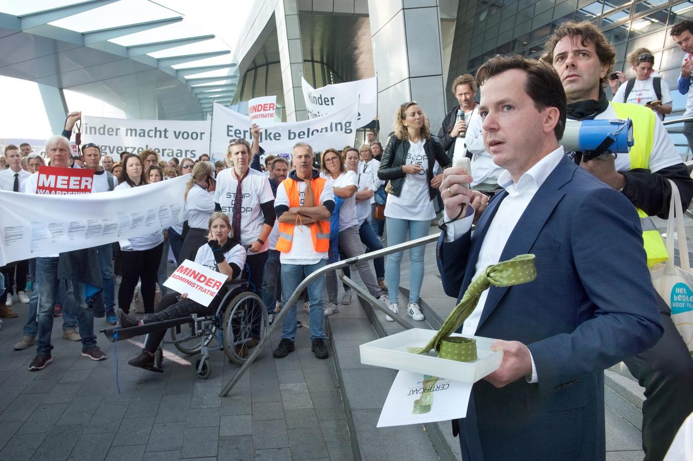 Martijn Kers van verzekeraar VGZ in Arnhem heeft net de Strakke Strop Award gekregen van de Actiegroep Fysiotherapie. Hij nodigt de massa voor een goed gesprek met een kop koffie maar de actievoerders eisen toezeggingen op papier.