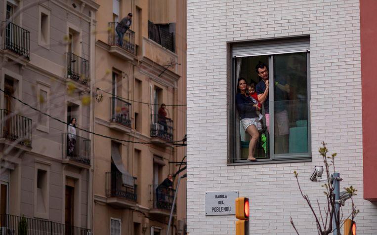Barcelona is in lockdown, eind maart 2020. Buren groeten elkaar vanaf hun balkon. Beeld AP