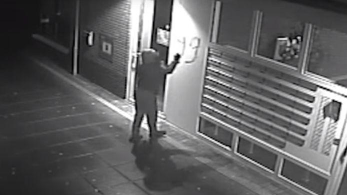 Een man spuit op 13 januari het getal 99 naast brievenbussen van appartementen in Kerkdriel, vlak voordat hij een handgranaat naar deze plek gooit.