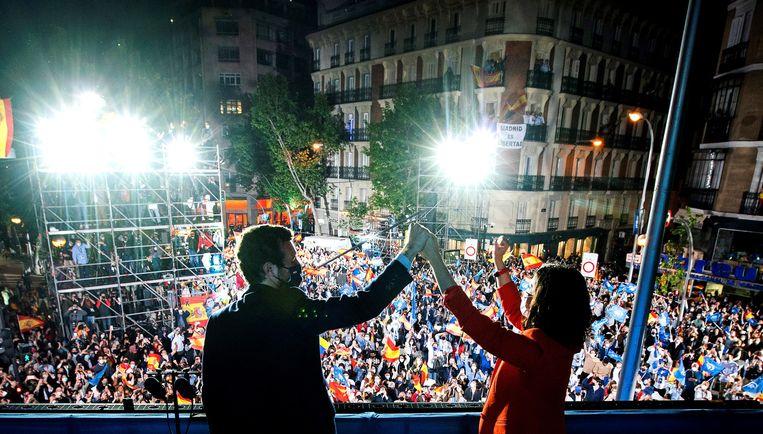 Regiopresident Isabel Diaz Ayuso (rechts) en de leider van de Volkspartij Pablo Casado (links) vieren hun verkiezingsoverwinning. Beeld EPA