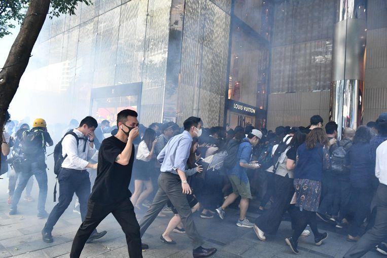 Zelfs in het financiële centrum van de stad moesten mensen vluchten voor het traangas. Beeld AFP