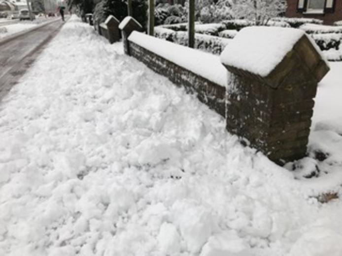 De stoep langs de Rijksweg in Malden ligt weer vol sneeuw nadat de sneeuwruimer voorbij is gereden.