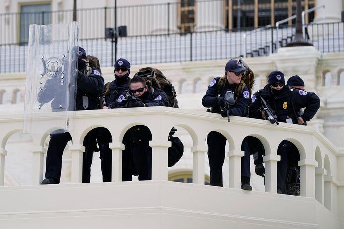 Capitoolpolitie beschermt het Amerikaanse parlementsgebouw met getrokken wapens.