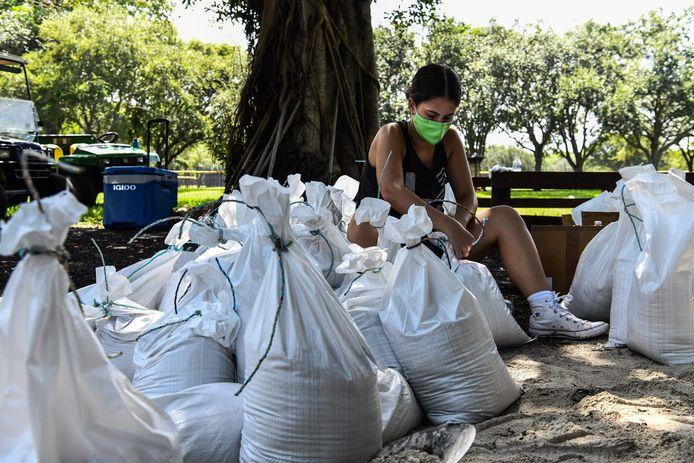 Een vrouw in Palmetto Bay, nabij Miami, prepareert zandzakken die bescherming moeten bieden tegen het oprukkende water.
