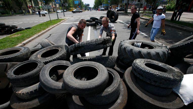 In Donetsk wordt een wegblokkade opgeworpen. Beeld REUTERS
