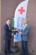 Burgemeester Joost van Oostrum neemt een aed in ontvangst van het Rode Kruis, die aan de Haarloseweg in Borculo hangt.