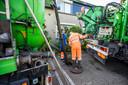 Patrick Kleywegt en een collega  bezig met het ontstoppen van het riool op de Schokkerwerf.
