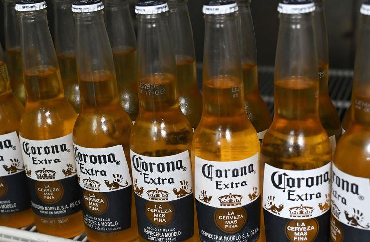 De bekende flesjes Corona-bier. De Mexicaanse brouwer legt de productie voorlopig stil. Beeld AFP