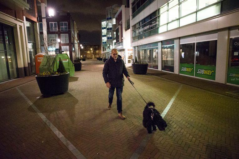 Een man laat zijn hond uit in een lege straat in Spijkenisse.  Beeld Arie Kievit