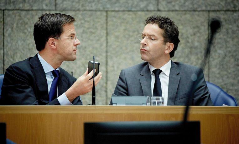Premier Mark Rutte (L) laat minister Jeroen Dijsselbloem (R) van Financiën op zijn mobiele telefoon een sms lezen. Beeld ANP