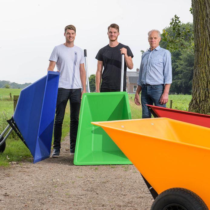 Oud-spits van FC Twente Jari Oosterwijk (midden) met zijn broer en vader en de nieuwe kruiwagen die ze op de markt hebben gebracht.